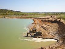 Vislock河,波兰-可以2日2018年:挖掘机用土壤装载翻斗车 土地在河石渣猎物运作  解压缩 图库摄影