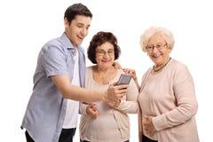 Visning för ung man något på telefonen till två äldre kvinnor Royaltyfri Fotografi