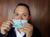visning för ung man och rymma en nyazeeländsk sedel av tio dollar arkivbild