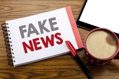 Visningen för handskriftmeddelandetext fejkar nyheterna Affärsidé för Hoax journalistik som är skriftlig på notepadanmärkningspap royaltyfria foton