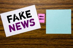 Visningen för handskriftmeddelandetext fejkar nyheterna Affärsidé för Hoax journalistik som är skriftlig på klibbigt anmärkningsp arkivbilder