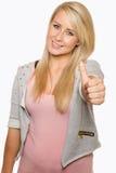 Visningen för ung kvinna tummar upp med hennes händer Fotografering för Bildbyråer