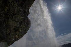 Visningen från insidan av en vattenfall med en ljus sol och solen blossar bakgrund Royaltyfria Bilder