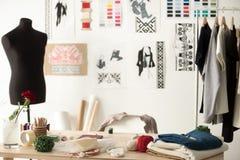 Visningslokal för modeformgivare med skyltdockan, arbetsskrivbordet och kläder royaltyfri bild