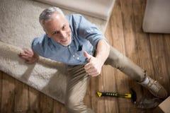 Visningtumme för hög man som är övre och ser kameran, medan sitta på golv Arkivfoto