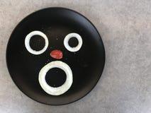 Viso umano sul piatto fatto dal pomodoro dell'uva e della cipolla immagini stock libere da diritti