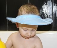 Little happy boy in the bathroom washes his head stock photos