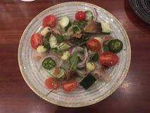 Vissen Crudo met droge vissenhuid en kleurrijke groenten stock afbeeldingen