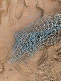 Vissen op het zand, vistuigen Groen netwerk op bruin zand royalty-vrije stock afbeeldingen