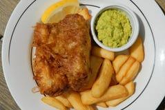 Vissen, spaanders en zachte erwten, traditionele Britse maaltijd stock afbeeldingen