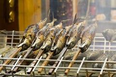 Vissen van de barbecue de stokvis geroosterde forel op voorraden met brandrook royalty-vrije stock foto's