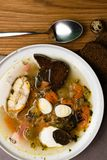 Vissen verse soep met groenten, kruiden en eieren in witte plaat, met lepel Soep met ingrediënten en kruiden voor het koken Grijz stock foto