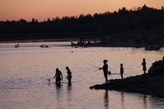 vissend bij het meer bij zonsondergang, achtergrond royalty-vrije stock afbeeldingen