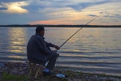 Vissende mens bij zonsondergang Royalty-vrije Stock Foto