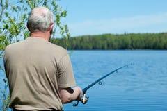 Vissende mens met een staaf stock foto's