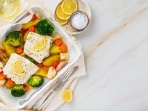 Vissenkabeljauw in de oven met groenten wordt gebakken - gezonde voedinggezondheid die stock afbeeldingen
