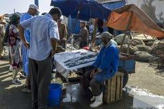 Vissenmonger aan het werk bij de bezige vissershaven van Essaouira in Marokko Stock Foto's