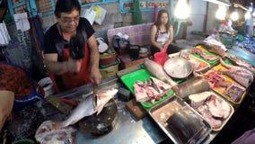 Vissenverkoper het hakken vissen bij natte marktkraam stock footage