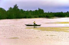 Visser alleen in zijn boot bij de rivier stock foto's