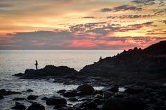 Visser bij klippenkust tijdens zonsondergang stock foto's