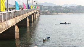 visser in bootvissen met schepnet dichtbij brug stock video