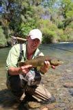 Visser die grote bruine forel in de rivier houden royalty-vrije stock afbeelding