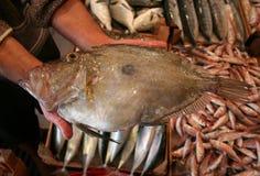 Visser die grote vissen in zijn hand houdt en bij de vissenmarkt toont Stock Foto