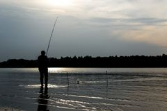 Visser die knie-zichdiep in het water bij zonsondergang in de rivier visserij bevinden royalty-vrije stock afbeelding
