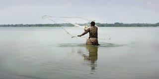 Visser die met netto vissen stock foto