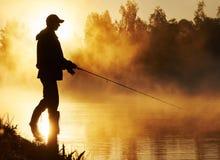 Visser die op mistige zonsopgang vissen Stock Afbeeldingen