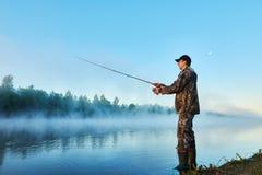 Visser die op mistige zonsopgang vissen Stock Foto