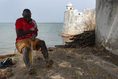 Visser die visnetten naast de Cacheu-Vesting in de stad van Cacheu, in Guinea-Bissau herstellen Royalty-vrije Stock Afbeeldingen