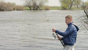 Visser die vissen vangen en visserijspoel op achtergrondrivierwater spinnen stock video
