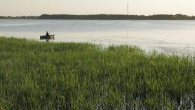 Visser in een boot die op een meer vissen stock videobeelden
