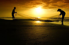 Visser en visster die tijdens zonsopgang werken Royalty-vrije Stock Foto's