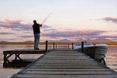 Visser en zonsondergang op het meer Stock Foto