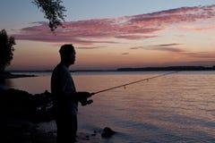 Visser met een donker silhouet tegen de achtergrond van een rivier Royalty-vrije Stock Fotografie