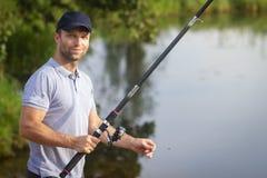 Visser met hengel op meerkust Mensenvangsten van vissen op rivier Vrije tijdsactiviteit Hobby in in openlucht Vissenjager royalty-vrije stock foto's