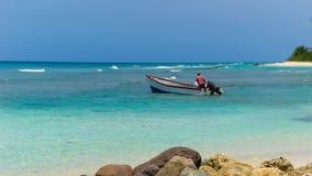 Visser met zijn boot klaar om in het Caraïbische overzees te vissen Stock Afbeeldingen
