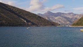 Visser op boot die vissen vangen Op achtergrondbergen van de Kotor-baai stock videobeelden