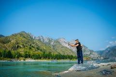 Visser op de bergrivier bij de aardige de zomerdag Forelvlieg die in de bergrivier vissen met bergen op achtergrond stock fotografie