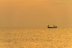 Visser op de boot over dramatische zonsondergang Stock Afbeeldingen