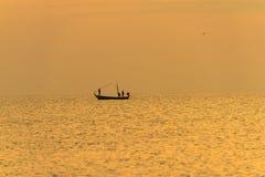 Visser op de boot over dramatische zonsondergang Royalty-vrije Stock Afbeelding