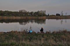 Visser op de stille avond op de rivier Tisa royalty-vrije stock fotografie