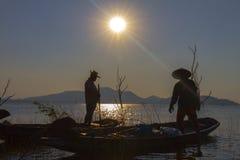 Visser op een houten boot met zonsondergangachtergrond stock foto's