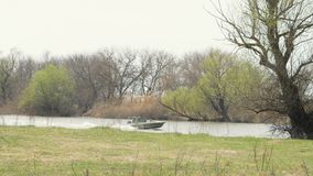 Visser op motorboot die op water op achtergrondbomen op rivierkust varen stock footage