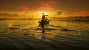 Visser van Aziatische mensen bij Meer in actie wanneer visserij Royalty-vrije Stock Afbeeldingen