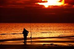Visserij in de zonsondergang Stock Afbeelding