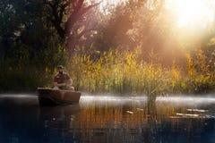 Visserij Mens die op een meer op boot vissen stock afbeeldingen