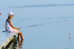 Visserij - mooi meisje die op de pijler vissen Stock Afbeelding